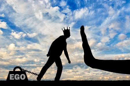 Silhouette of a selfish man with a crown on his head draws a heavy load - the ego and a large hand stop it. The conceptual scene of selfishness as a social problem