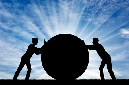 Two selfish men push the big ball, each in its own way, not yielding to each other. Conceptual scene of selfish people Reklamní fotografie