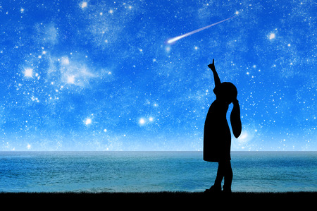 Silueta, niña un niño de pie junto al mar mirando el cielo estrellado y señalando con el dedo el meteorito volador. Imagen conceptual de los sueños y fantasías de los niños