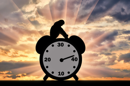 Silhouette of a sad woman sitting on a clock where the arrow shows almost 40 years old. Conceptual image of impending menopause in women Standard-Bild - 108359163