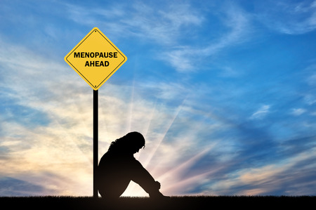 Sad woman sitting in front of a road sign menopause ahead. A conceptual image of a woman's imminent menopause 스톡 콘텐츠 - 108359167