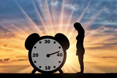 Sad woman standing at the clock hand which shows almost 40 years. Conceptual image of impending menopause in women Standard-Bild - 108359170