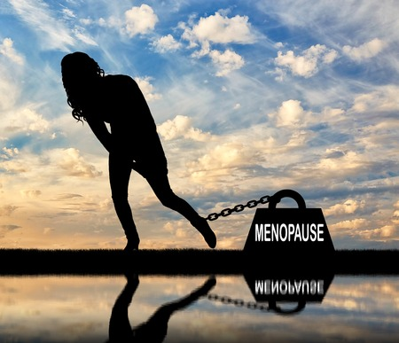The silhouette of a sad woman and a heavy load of menopause is chained to her leg. Conceptual image of menopause in women Stock fotó - 108359174
