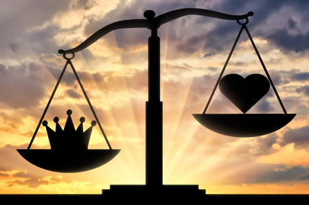 The silhouette of the scales which bowl is inclined towards the crown, not the heart, against the background of the sunset. Concept image of selfishness Stock Photo
