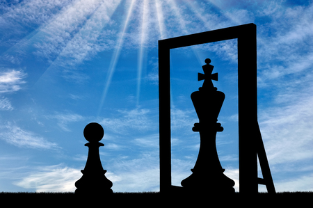 Silhouette of a narcissistic pawn, sees himself in the reflection of the mirror queen. The concept of narcissism Stock Photo
