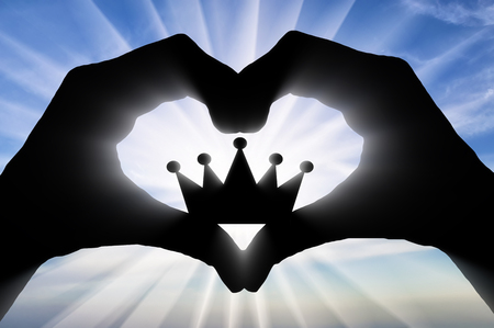 The hands of a man hold a crown, showing that he likes this symbol of the heart. Concept of narcissism Imagens