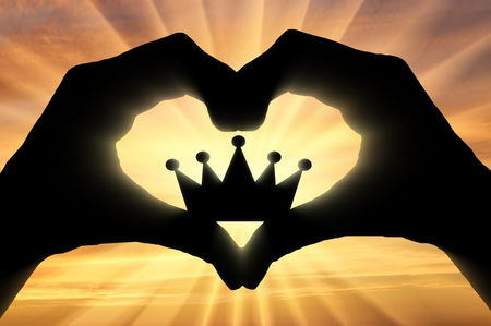 Hands of a man hold a crown, showing that he likes this symbol of the heart. The concept of narcissism and selfishness Imagens