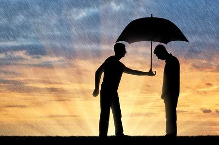 Un hombre altruista comparte un paraguas con otro hombre triste de pie bajo la lluvia. Concepto de altruismo en la sociedad Foto de archivo