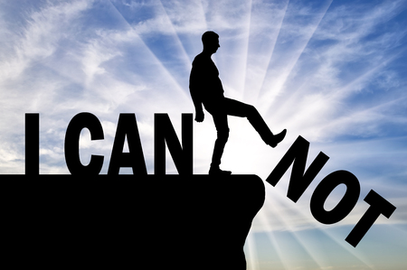 A man standing on a cliff pushes the word - I can not, he achieves the word - I can. Concept of motivation and success