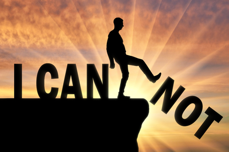 A man standing on a cliff pushes the word - I can not, he achieves the word - I can. The concept of motivation and positive thinking Imagens