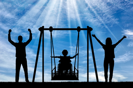 Silhouette of happy child is disabled in a wheelchair on an adaptive swing with mom and dad. have fun together. Concept of the lifestyle of children with disabilities and adaptive equipment for them