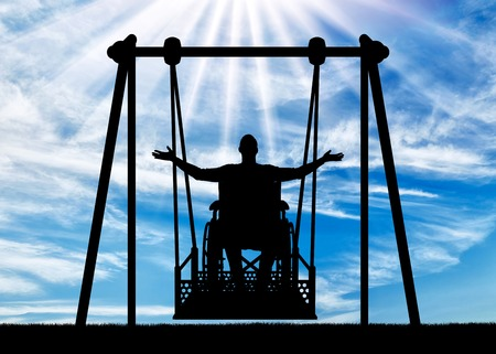 Silhouette of a happy man is a disabled person in a wheelchair on an adaptive swing for disabled people. Concept of the lifestyle of people with disabilities Imagens