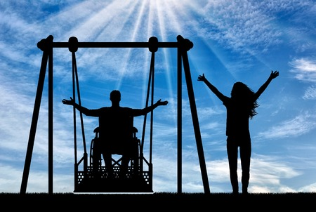 Silhouette of happy couple, man in wheelchair for disabled person on adaptive swing and healthy woman nearby. The concept of the lifestyle of people with disabilities