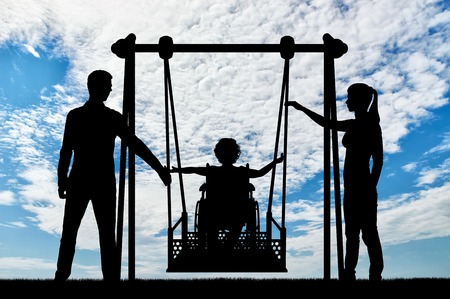 Silhouette of a happy child is a disabled person in a wheelchair on an adaptive swing. Mom and Dad swing it. The concept of the lifestyle of children with disabilities