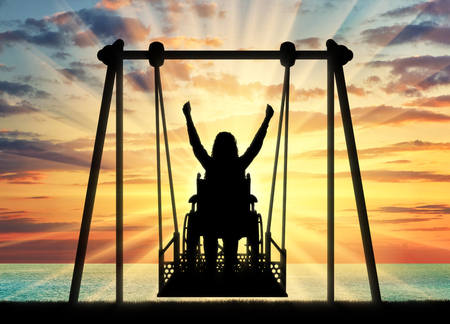 Silhouette of a happy woman is a disabled person in a wheelchair on an adaptive swing against the backdrop of a sea sunset. Concept of the lifestyle of people with disabilities