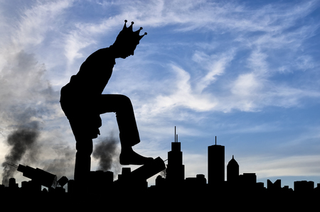 Silhouette of a man selfish giant with a crown on his head, destroys the city on your way - it does not stop. The concept of a large ego - a social problem