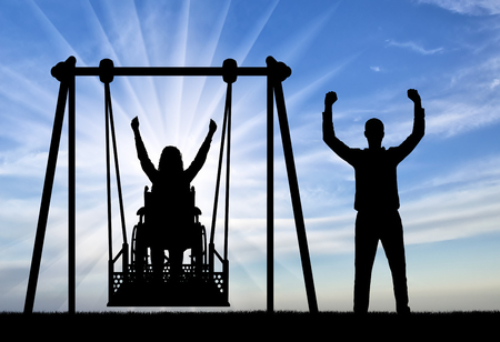 Silhouette of a happy couple, a woman wheelchair user on an adaptive swing and a healthy man nearby. Concept of the lifestyle of people with disabilities