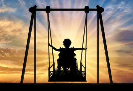 Happy child is disabled in a wheelchair on an adaptive swing for disabled children. Lifestyle of children with disabilities