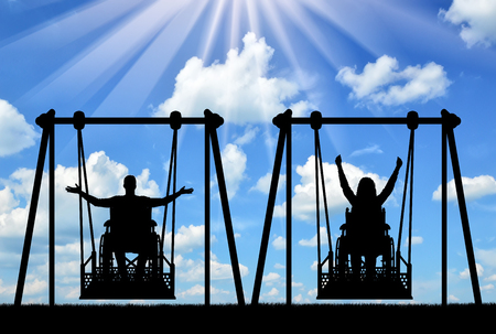 Happy couple, a man, a disabled person and a disabled woman in a wheelchair ride on an adaptive swing. The concept of adaptive equipment for people with disabilities