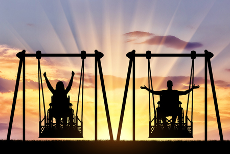 Happy couple, a man is a disabled person and a disabled woman in a wheelchair on an adaptive swing. The concept of lifestyle for people with disabilities and equipment for people with disabilities