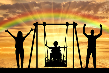 Silhouette of happy child is disabled in a wheelchair on an adaptive swing with mom and dad on the background of a sea sunset with a rainbow. The concept of lifestyle of children with disabilities and their support