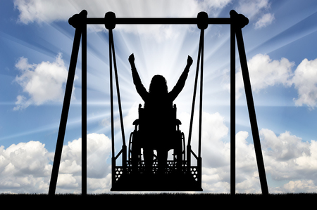 Silhouette of a happy woman is a disabled person in a wheelchair on an adaptive swing for disabled people. The concept of the lifestyle of people with disabilities Imagens