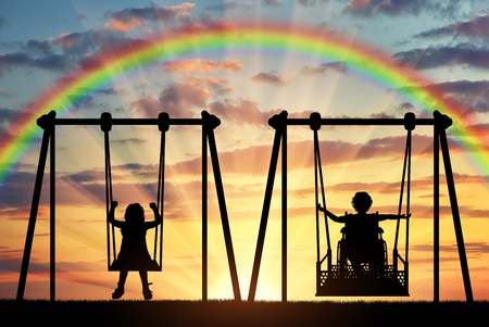 Happy child is a disabled person in a wheelchair riding an adaptive swing next to a healthy child together. Concept of adaptive equipment for children with disabilities