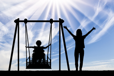Happy child is disabled in a wheelchair on an adaptive swing for disabled children with mom. Lifestyle and support for disabled children