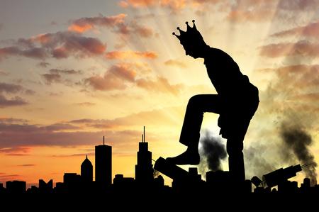 Il grande uomo egoista con una corona distrugge la città sulla sua strada. Grande concetto di ego Archivio Fotografico