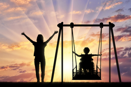 Lifestyle and support for disabled children. Happy child is disabled in a wheelchair on an adaptive swing for disabled children with mom.