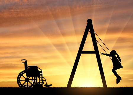 Silhouette of a child disabled girl on a swing next to a wheelchair on a sunset background. Concept of children with disabilities and their leisure