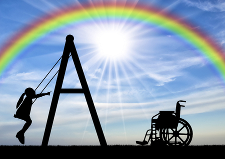 Silhouette of a child disabled girl on a swing next to a wheelchair on a background of the sky with a rainbow. Concept of playing children with disabilities Imagens