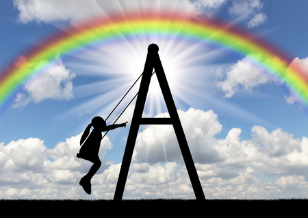 A girl child is rolling on a swing against the sky with a rainbow. Concept of a happy childhood