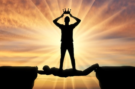 Selfish man puts a crown on his head, he stands on a man in the form of a bridge over a precipice. Concept of selfishness Imagens
