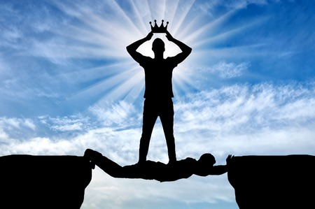 Selfish man puts his crown on his head, he is on the man in the form of a bridge over the abyss. Concept of selfishness in relationships between people