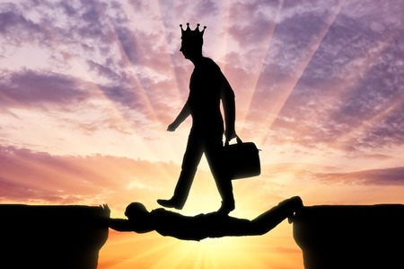 Selfish man with a crown on his head is walking over a man in the form of a bridge over an abyss. The concept of selfishness