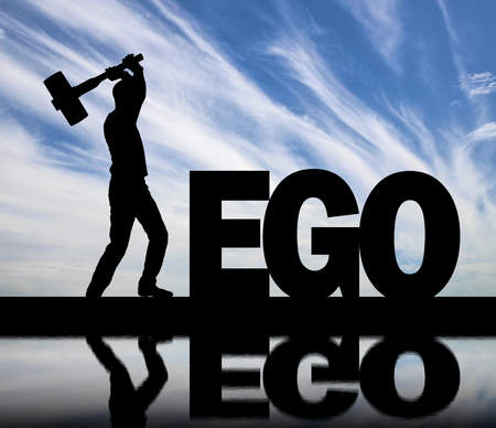 Man with a big sledgehammer in his hands intends to destroy the word ego by the river with its reflection. Concept of choosing to be selfish or not