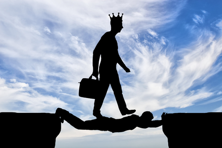 Selfish man with a crown on his head is walking over a man in the form of a bridge over an abyss. Concept of selfishness in business
