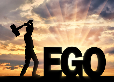 Man with a hammer in his hand intends to destroy the word ego. Concept of choosing to be selfish or not