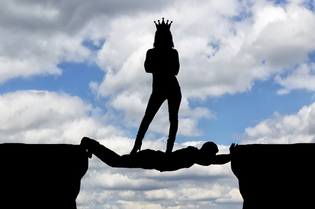 Selfish woman with a crown standing on a man in the form of a bridge over an abyss. Concept of selfishness in business