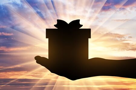 Altruism concept. Silhouette of a hand giving a gift on a sunset background