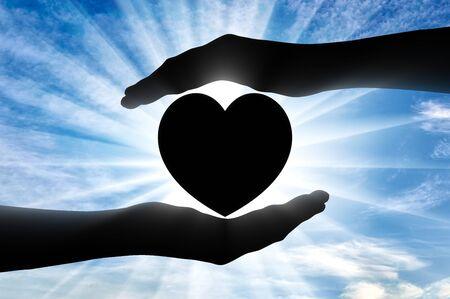 Altruism concept. Silhouette of hands protecting heart symbol Standard-Bild - 131492077