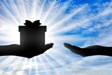 Altruism. Silhouette of a hand giving a gift and a hand receiving a gift Reklamní fotografie