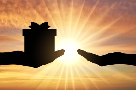 Altruism concept. Silhouette of a hand giving a gift and a hand receiving a gift on a sunset background