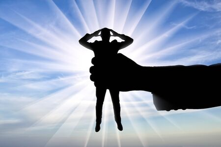 Workplace bullying concept. Silhouette of a man's hand holds a man in a fist