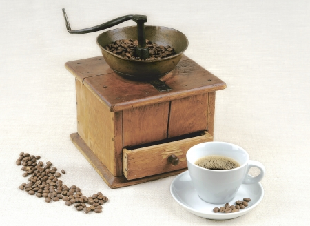 An old coffee mill, coffee beans and a cup of coffee photo