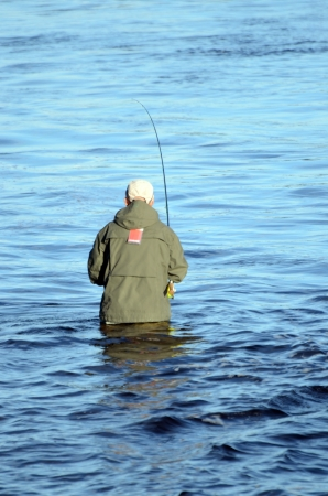 A man stands in the water and fishing with a fly fishing rod photo