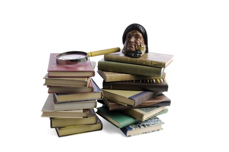 Books and a magnifying glass isolated on a white background photo