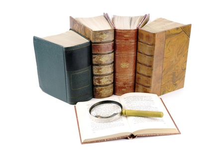 Books and a magnifying glass isolated on a white background