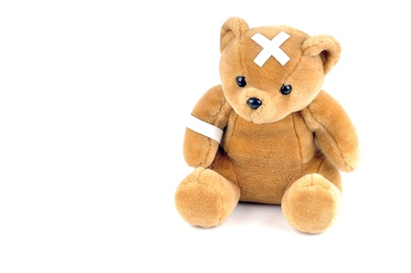 disease patients: A Brown Teddy bear with sticking plaster against a white background Stock Photo
